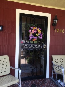 A steel security storm door with decorative iron work.