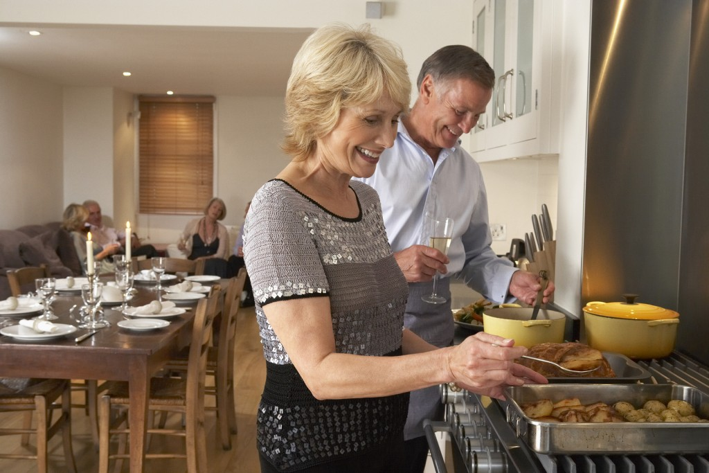 Couple Preparing Food For A Dinner Party new kitchen